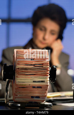 Businesswoman at desk working late with her rolodex card index, NYC, USA - Stock Image