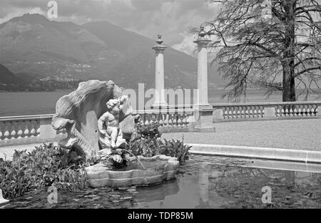 BELAGGIO, ITALY - MAY 10, 2015: The Villa Melzi on the waterfront of Como lake and the little fountain in the gardens. - Stock Image