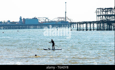 Brighton UK 30th April 2019 - A paddle boarder and swimmer enjoy the warm sunny weather off Hove beach near the West Pier this morning with it forecast to reach into the high teens in some parts of the South East today. Credit: Simon Dack/Alamy Live News - Stock Image