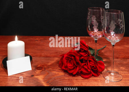 Beautiful etched wine glasses with red roses and white candle on wooden table and dark background. Valentines, Mothers Day, Easter, Christmas, Wedding - Stock Image