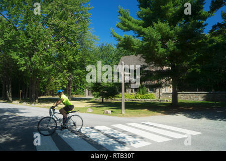 Cyclist passing by Jordan Pond Gate House in Acadia National Park, Maine, USA. - Stock Image