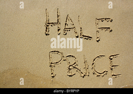 'Half Price' written out in wet sand. Please see my collection for more similar photos. - Stock Image