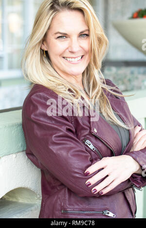 Portrait of a woman smiling outside. - Stock Image