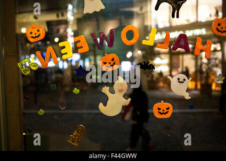 Halloween window sticker decorations on window at night - Stock Image