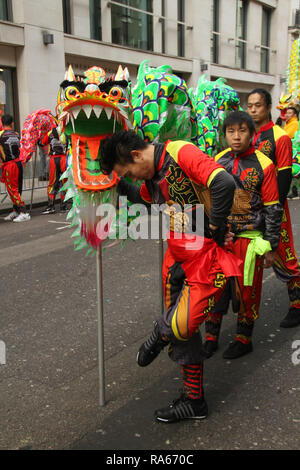 London, UK. 1st January, 2019. Performers from the london Chinatown Chinese Association seen ahead of the New Years parde at Berkley Square. About 8,000 performers representing the London boroughs and over 20 countries from across the globe take part on the annual New Years Parade on the street of London on January 1, 2019. The parade will as is custom include dancers, acrobats, cheerleaders, marching bands, historic vehicles and huge balloons making their way from Green Park Tube station to Parliament Square. Credit: david mbiyu/Alamy Live News Credit: david mbiyu/Alamy Live News - Stock Image