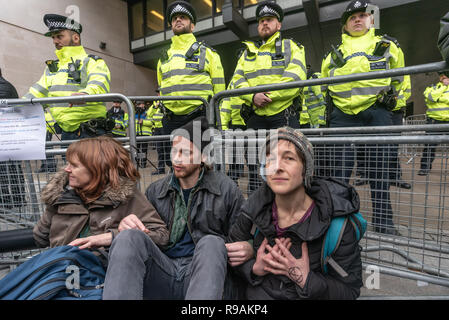 London, UK. 21st December 2018. Climate campaigners from Extinction Rebellion sit down in front of the BBC Plaza calling it to stop ignoring the climate emergency & mass extinctions taking place and promoting destructive high-carbon living through programmes such as Top Gear and those on fashion, travel, makeovers etc. The protest, organised by the Climate Media Coalition (CMC) and its director Donnachadh McCarthy brought mannequins wrapped in white cloth to the BBC representing the bodies of a Greek village killed by fire. Peter Marshall/Alamy Live News - Stock Image