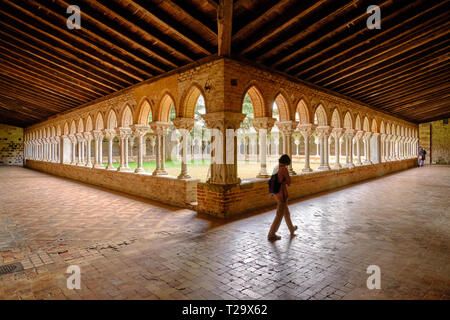 Moissac Abbey monastery courtyard in Moissac with a pilgrim visit. View of the of archways that lines the yard as seen from one corner, under late aft - Stock Image