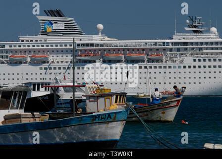 Contrast, modest fishing boats beside luxurious transatlantic ship, Armação de Búzios, Rio de Janeiro state, Brazil. - Stock Image