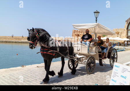 Chania, Crete, Greece. June 2019. Tourists taking a ride in an open carriage around the Old Venetian Harbour in Chania - Stock Image