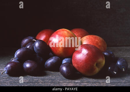 Fresh nectarines and plums or damsons on a dark wooden background, copy or text space - Stock Image