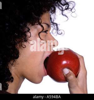 Young Woman With Curly Hair Eating Apple - Stock Image