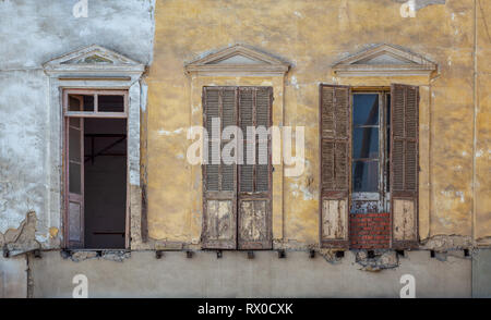 Aged abandoned retro vintage grunge house facade with broken windows and weathered shutters - Stock Image