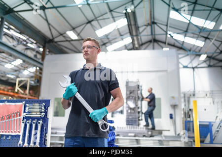 Engineer holding large spanner in gearbox factory - Stock Image
