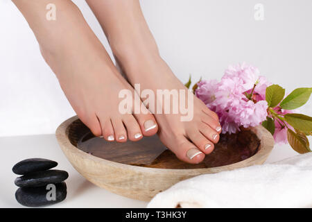 Girl bare feet on wooden bowl with water and decorative flower and stone in beauty and spa studio. Pedicure and relaxation foot concept. Close up - Stock Image