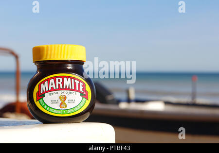 A jar of Marmite set by inshore fishing boats on the North Norfolk coast. - Stock Image