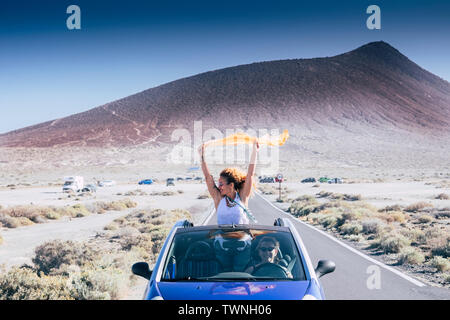 Freedom and travel concept for independent adult caucasian women together with convertible car - people traveling and enjoying tie friendship - drive - Stock Image