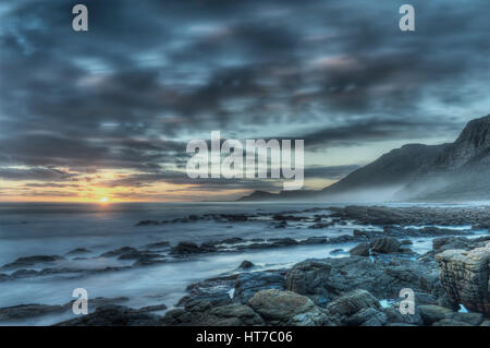 Sunset rocky ocean - Stock Image