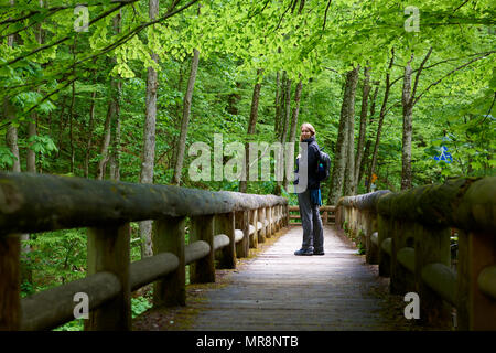 Caucasian female backpacker looking back at the camera and smiling on passageway surrounded by forest. - Stock Image