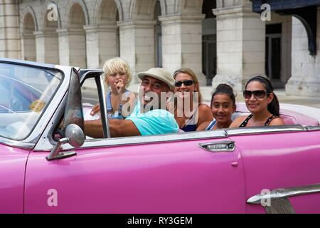 Cuba, La Havana, Parque central, cap driver with his cuban and american passengers in his old american car pink and convertible - Stock Image