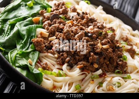 Dandan noodles or dandanmianwith minced meat is dish originating from Chinese Sichuan cuisine closeup in a plate on the table. horizontal - Stock Image
