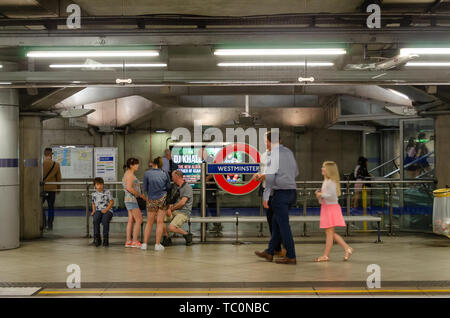 People sit on a bench on the platform at Westminster London Underground Station - Stock Image
