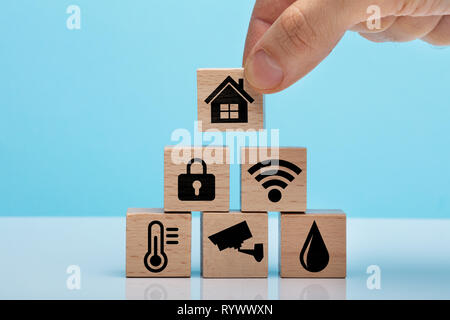 Hand Placing Wooden Block With Home Icon Over Stacked Home Automation Icons Wooden Block - Stock Image