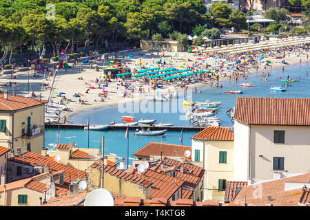 beach of the Cote d'Azur with tourists with sunbeds and umbrellas on the hot summer day - Stock Image