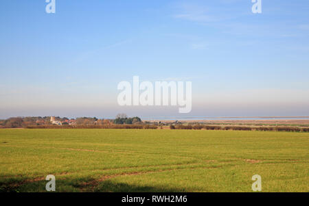 A view over farmland to the village of Morston and Blakeney Point from the Downs at Blakeney, Norfolk, England, United Kingdom, Europe. - Stock Image