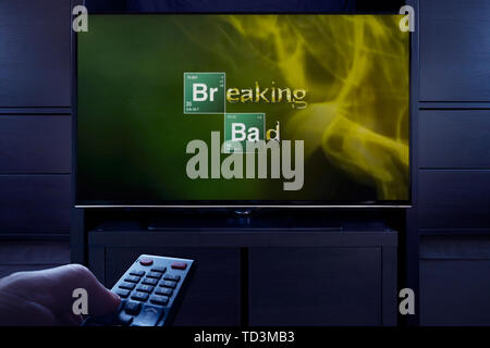 A man points a TV remote at the television which displays the Breaking Bad main title screen (Editorial use only). - Stock Image