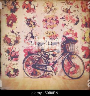 Bicycle with flowers in basket and flower wallpaper - Stock Image