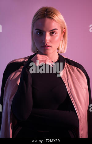 High Fashion model woman in colorful bright lights posing, portrait of beautiful girl wear sport tracksuit. Fashionable pink colorful studio lights - Stock Image