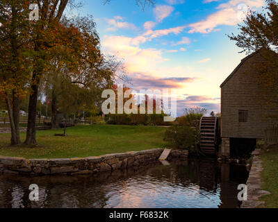 Historic Dexter Grist Mill, Sandwich MA. Cape Cod Massachusetts USA wooden water wheel and millrace in autumn blue - Stock Image
