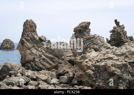 Italy Sicily Catania Aci Trezza Faraglioni basalt rocks the Isole dei Ciclopt nature reserve of Homer fame - Stock Image