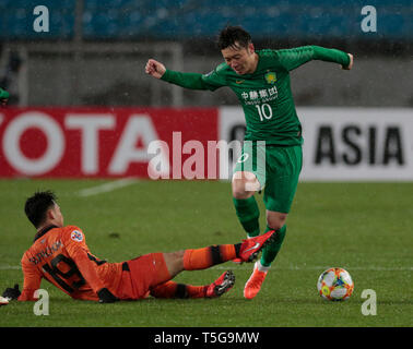 Beijing, China. 24th Apr, 2019. Zhang Xizhe (R) of Beijing Guoan FC vies with Supachok Sarachar of Buriram United during the group G match between China's Beijing Guoan FC and Thailand's Buriram United at the 2019 AFC Champions League in Beijing, capital of China, April 24, 2019. Credit: Ding Xu/Xinhua/Alamy Live News - Stock Image