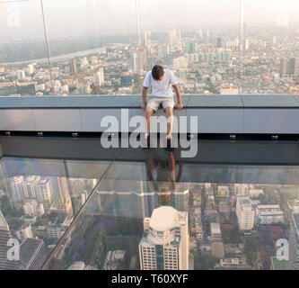 THAILAND, BANGKOK - NOVEMBER 25, 2018: A man sits on a glass floor on the roof of a King Power Mahanakhon building. Currently, it is the tallest build - Stock Image