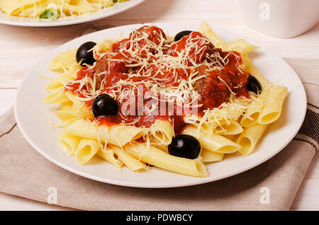 Penne pasta with meatballs in tomato sauce in a white plate - Stock Image
