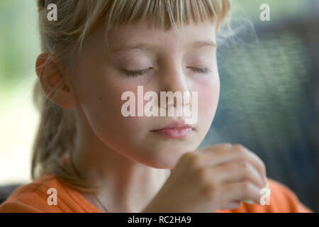 Close up young girl with eyes closed - Stock Image
