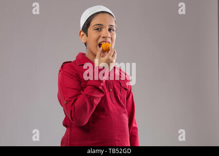 Young Muslim boy wearing cap eating sweets - Stock Image
