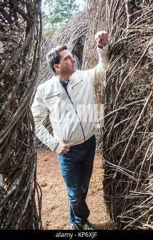 Handsome caucasian man looking at wood statues, made by an artist in botanical gardens. - Stock Image
