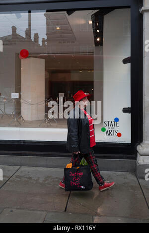 A shopper walks past a window display that is part of a design theme called 'State of the Arts', at the Selfridges department store on Oxford Street, on 4th March 2019, in London England. State of the Arts is a gallery of works by nine crtically-acclaimed artists in Selfridges windows to celebrate the power of public art. Each of the artists are involved in creating a site-specific artwork at one of the new Elizabeth line stations as part of the Crossrail Art Programme. - Stock Image