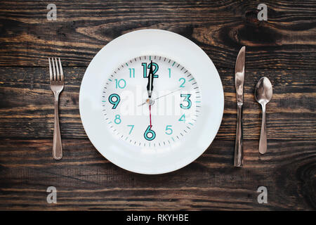 Twelve hour intermittent fasting time concept with clock on plate over a rustic wooden table / background. Top view. - Stock Image