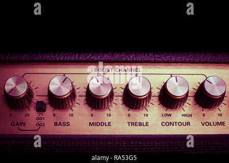 vintage amplifier six knobs horizontal closeup, copy space on top, magenta, isolated - Stock Image