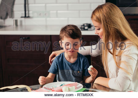 Happy caring young blonde woman having lunch with her son at kitchen, eating together and discussing future fest celebration - Stock Image