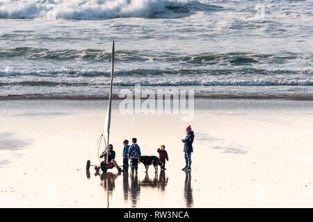A father setting up his Ludic Seagull sand yacht as the rest of his family watch on Fistral Beach in Newquay Cornwall. - Stock Image