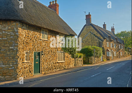 Streetscene in the pretty Dorset village of Abbotsbury, with thatched cottages under a blue sky. - Stock Image