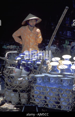 Woman china dealer with bike with a huge amount of china Vietnam - Stock Image