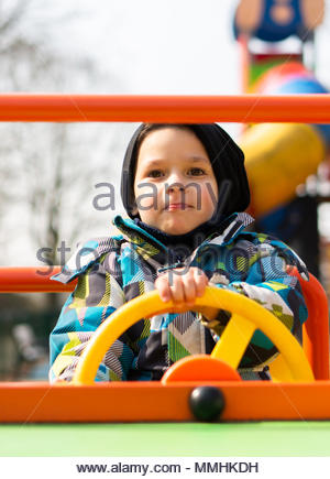 4 years old boy sitting in a spring car at a playground in Poznan, Poland - Stock Image