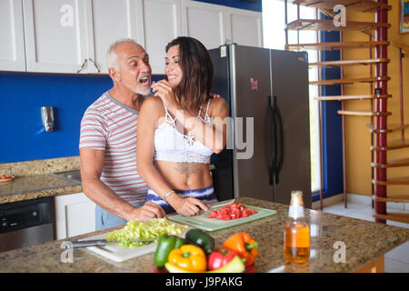 Young woman and older man enjoying to cut vegetables and feeding each other in their apartment kitchen - Stock Image