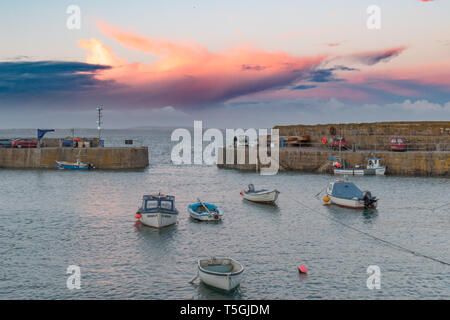 Mousehole, Cornwall, UK. 24th Apr, 2019. UK Weather. Sunset at Mousehole harbour, with the red cloud almost looking like a plane taking off over the sea. Credit: Simon Maycock/Alamy Live News - Stock Image
