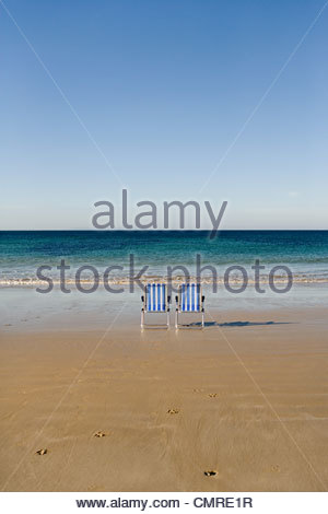Two deckchairs by the sea - Stock Image